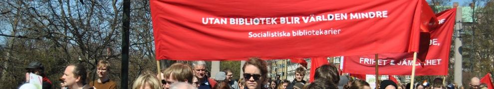 """Demonstrationståg. En röd banderoll syns med texten """"Utan bibliotek blir världen mindre: socialistiska bibliotekarier"""""""
