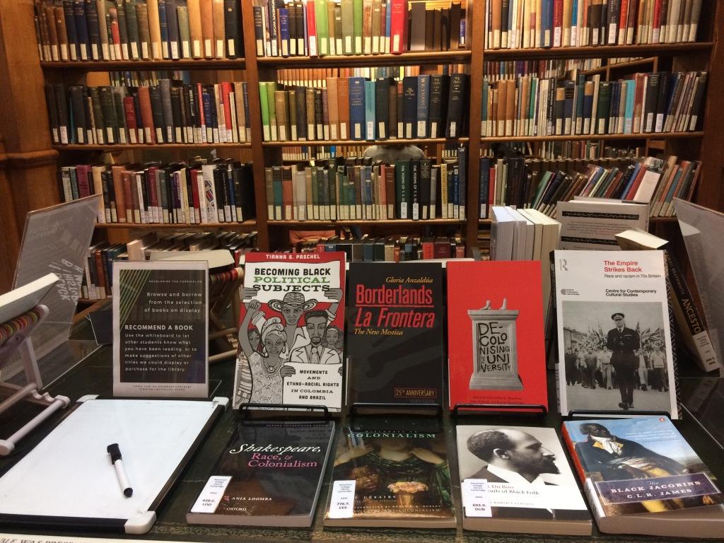 Skyltning av böcker på ett bord i ett bibliotek med tema dekolonisering.