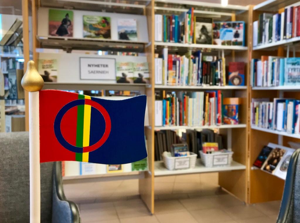 Biblioteksrum, böcker i bakgrunden, en liten samisk flagga i trä i förgrunden.